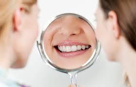 Två kvinnor tittar i en spegel där den ena kvinnans leende syns